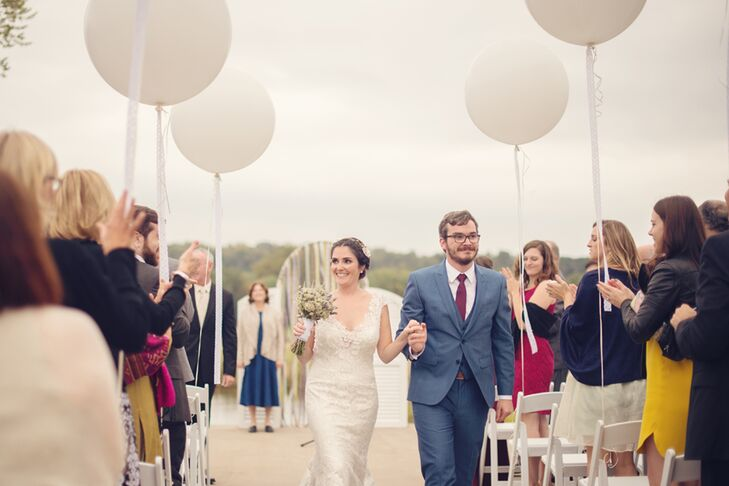 """After searching through Pinterest, Erin and Cory picked out a festive suit for his wedding day look.  He wore a """"postman"""" blue suit and a burgundy tie with a subtle, matching blue pattern. His groomsmen, however,  stood out in navy blue suits and pale green ties."""