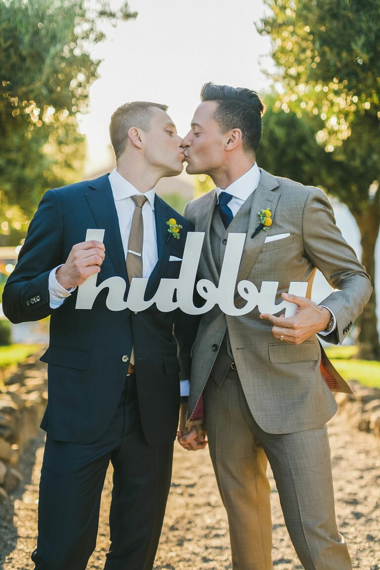 gay couple holding hubby sign at wedding ceremony
