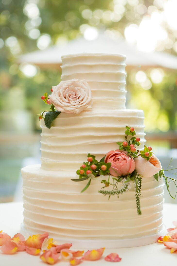 Carrie's Cakes designed the three-tier, somewhat rough-frosted dessert, which was adorned with blush pink blossoms and sprigs of greenery.