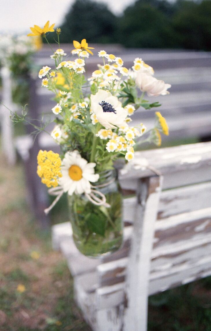 Mason jars filled with daisies, anemones and wild flowers hung from bench pews to serve as aisle decorations at the ceremony.