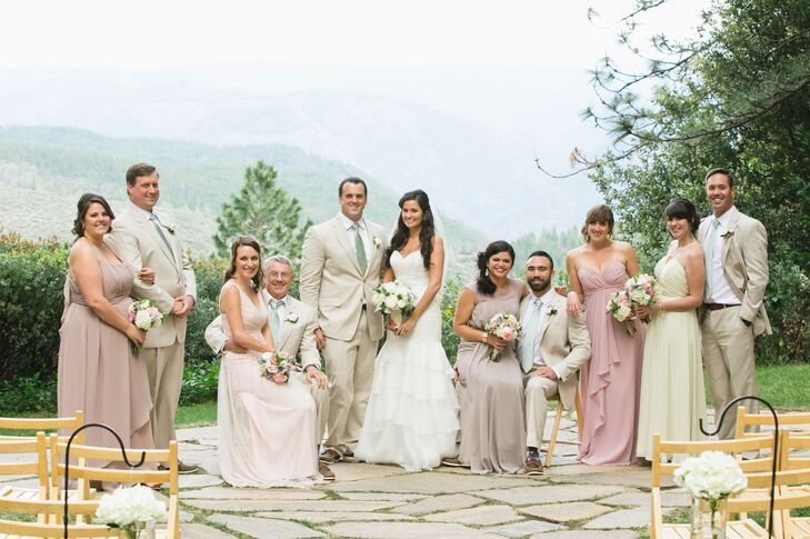 """Raquel and Sean stood together with their wedding party, with bridesmaids dressed in pastel-colored dresses and groomsmen wearing tan suits with sage green ties. """"I chose tan linen suits for the men with mint green ties,"""" Raquel says. """"The bridesmaids picked their own dresses in muted pastels of cream, pink and lavender."""""""