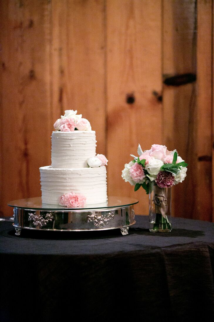 """The two-tiered ivory wedding cake topped with pink and white flowers was positioned on an elegant silver stand at the reception. """"Dessert was my favorite part, and we did a small traditional cake with strawberry filling,"""" Raquel says. """"We also did a s'mores bar, where guests could roast their own marshmallows, and also a cheesecake bar, since I love cheesecake."""""""