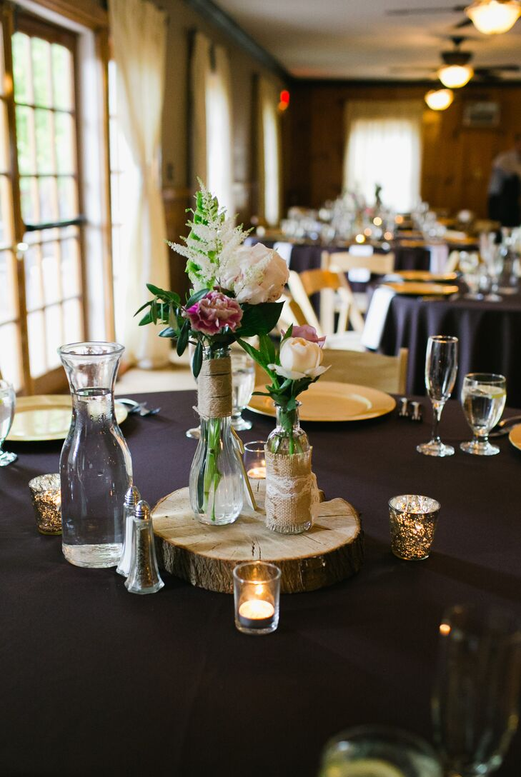 The reception took place on the middle floor inside the lodge, where dining tables were decorated in plum-colored linens and set with gold plates. The middle of the table was decorated with carnation, peony, rose and veronica flowers arranged inside glass vases, which were wrapped with burlap and lace. The centerpieces were positioned on top of wooden slabs and surrounded by candle votives.
