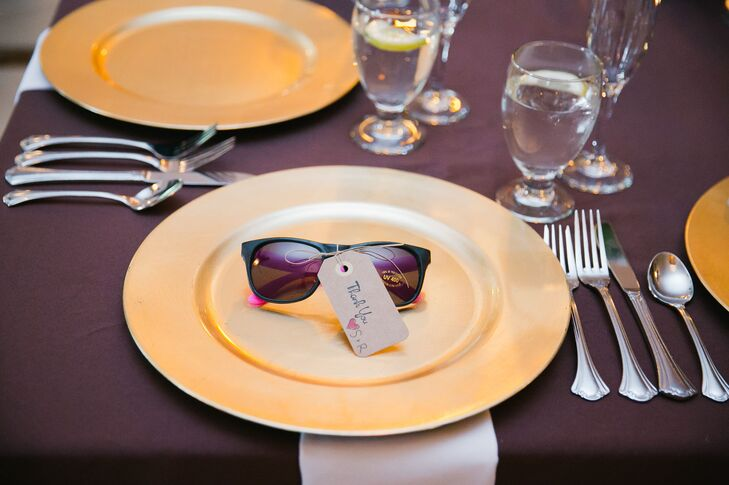 At the reception, plum-colored dining tables were set with gold plates and white napkins. The couple gave out neon sunglasses as wedding favors at each seat, which were used throughout the evening's festivities.