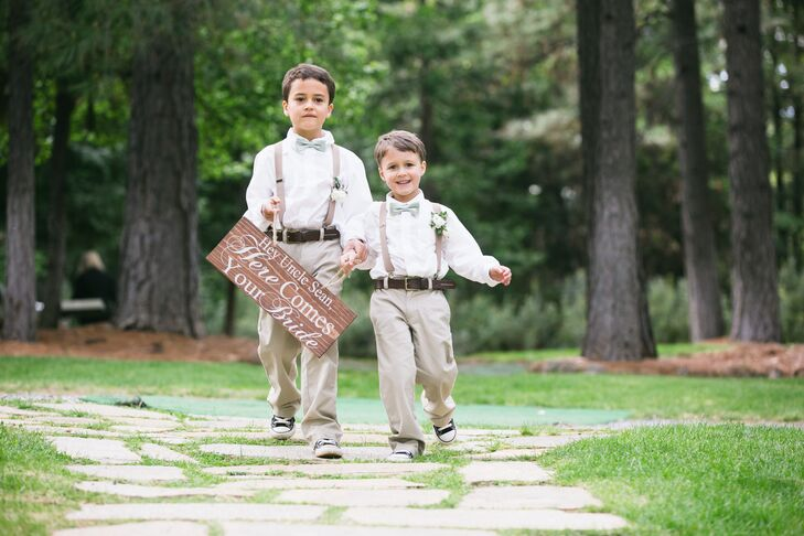 """The ring bearers walked down the aisle wearing matching khaki pants with brown suspenders, and a white button-up shirt complemented by a green bow tie. They each wore an ivory rose boutonniere pinned to their suspender strap and held a wooden wedding sign that read """"Hey, Uncle Sean, Here Comes Your Bride."""""""