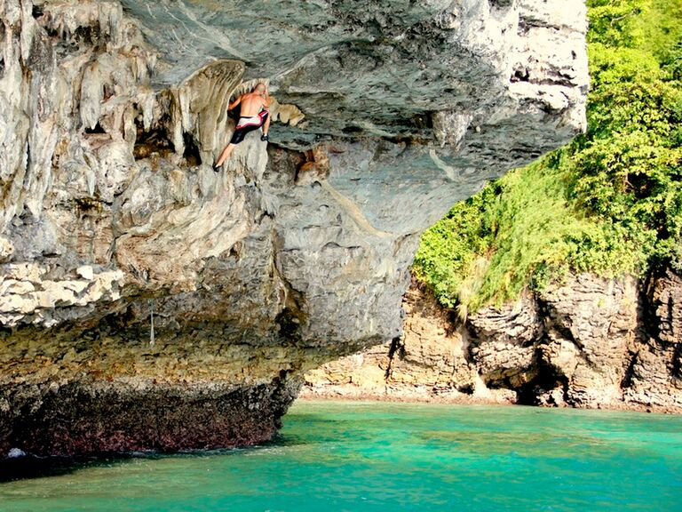 A man deep water solo climbing and diving