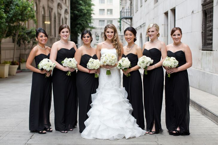The bride stood with her bridesmaids, who were wearing long floor-length black strapless dresses with sweetheart cuts, purchased from The Dessy Group. The bridal party all held their ivory rose and hydrangea bouquets made by Lavenders Flowers.