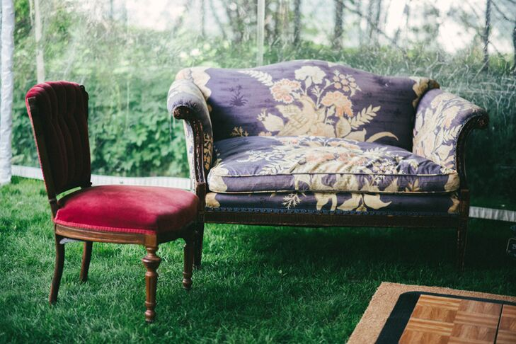 A vintage settee in a floral fabric and a red vintage velvet slipper chair helped create a small lounge area.