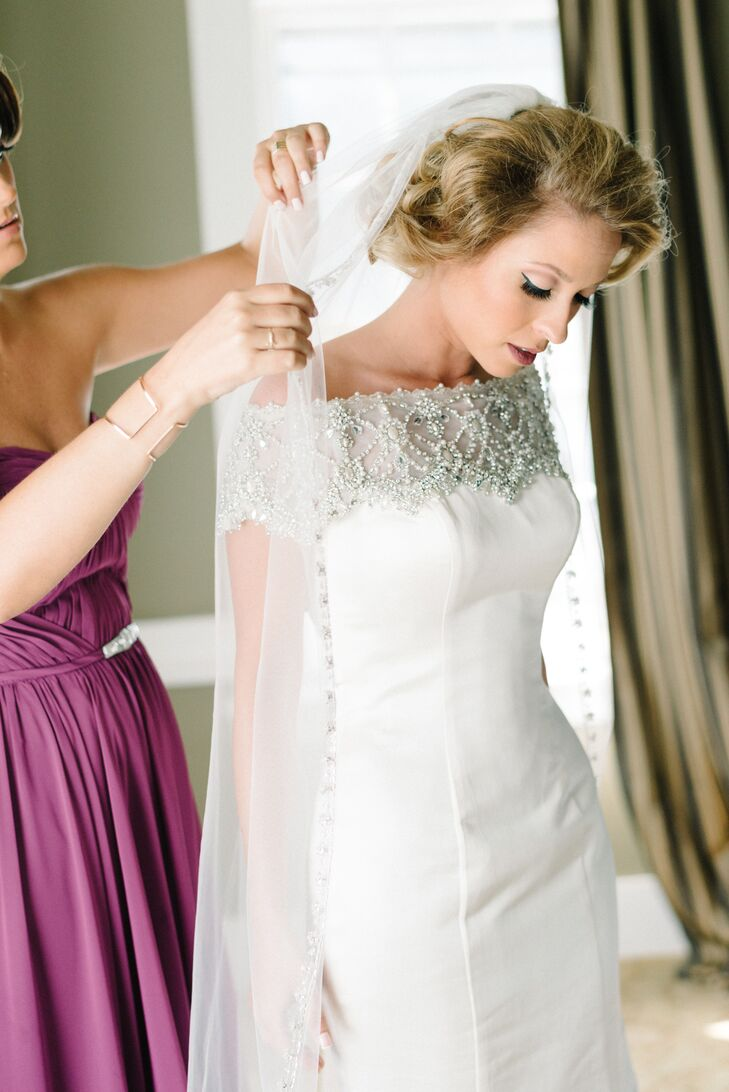 """Sarah's love for vintage and glamorous styles definitely came out in her dress. That morning, she slipped on a chic Justin Alexander mermaid-style gown with intricate beading throughout its off-the-shoulder neckline. """"The beading also cascaded down the back of the dress, which then trailed off with buttons all the way down the train,"""" she says. """"It screamed old Hollywood."""" To highlight the ornate look, she paired it with a simple floor-length veil trimmed in similar beading and a bold, curled faux bob worthy of the 1940s."""