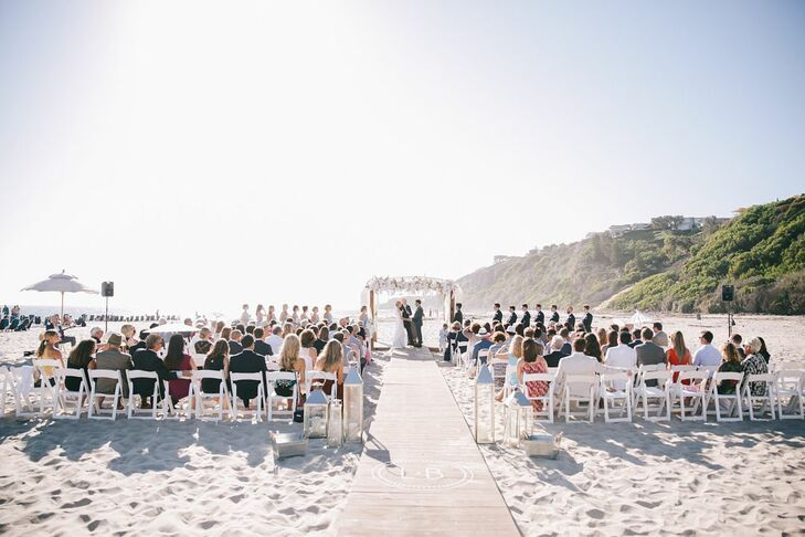 A custom wooden walkway imprinted with Leah and Brian's initials served as the aisle, which led the couple to an arch made with white blossoms and draped with white fabric.
