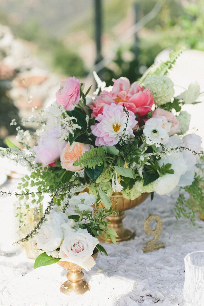 "Megan from Honey & Poppies created a series of textured, full arrangements of dahlias, peonies, garden roses, ferns, lilacs and hydrangeas in shades of pink, ivory and peach that brought the reception tables to life. ""Flowers really add a big romance factor to a wedding's atmosphere,"" Sarah says."
