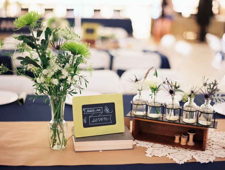 """Allison and Matthew created all of the centerpieces with craft paper, vases, books, chalkboards and sewing spools. """"We liked the relaxed look of the textured table settings, making each it's own a little interesting,"""" Allison says."""