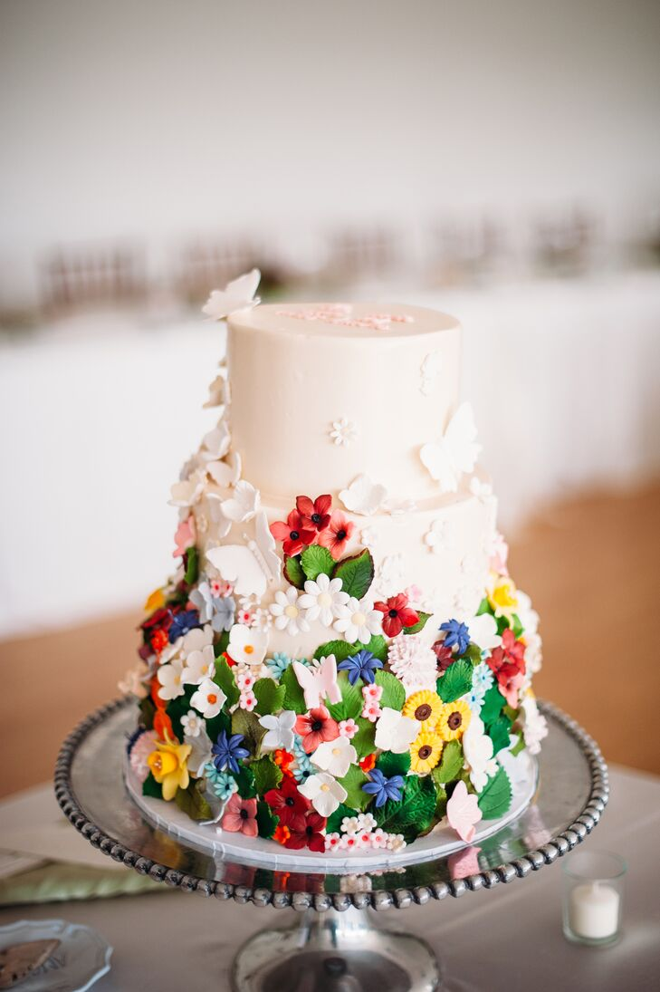 The three-tier ivory vanilla wedding cake was filled with layers of dulce de leche and fudge, frosted with Italian buttercream and decorated with brightly colored wildflowers.