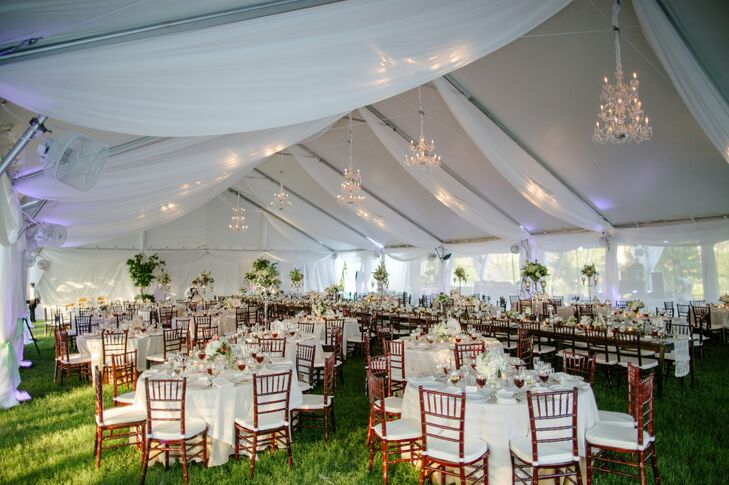 """At the reception, the couple and their wedding party sat at a long row of vintage vineyard tables that ran through the middle of the tent. They were topped with white lace runners, grapevine, silver candelabras, mercury glass containers, votives and bottles. """"I'm probably a bit partial, but it was the most beautiful thing I've ever seen,"""" Kayla says of their fabric-draped dinner tent. """"It was my dream come true!"""""""