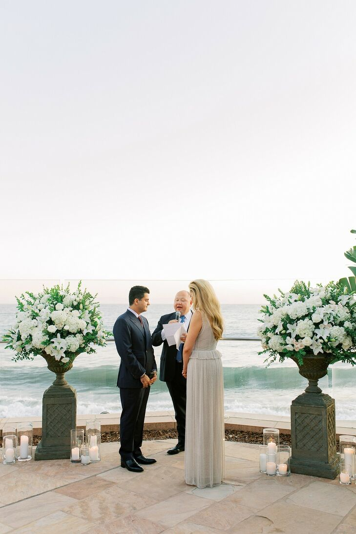 Elegant Waterfront Ceremony with White Flower Arrangements and Candles