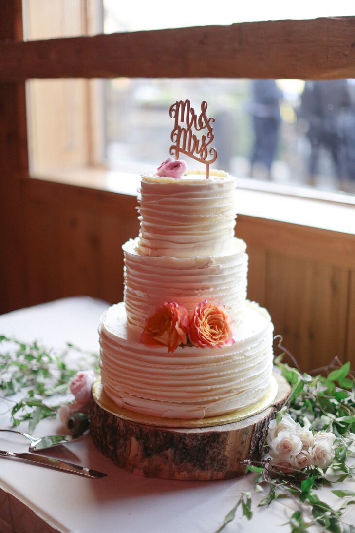 Nicole and Alex's three tier buttercream wedding cake was finished with fresh flowers, jasmine vine and a wooden Mr. and Mrs. topper.