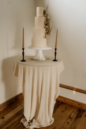 Simple Three-Tier Wedding Cake on Table with Taper Candles