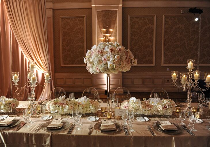 """Our reception was in the Grand Ballroom, where everything from the carpet print to the chandeliers matched the palette and vibe we wanted,"" Sarah says. She outfitted the Waldorf Astoria in Orlando, Florida with florals of different heights in mercury-glass vessels, along with and crystal candelabras with candlesticks that ""matched perfectly with our neutral palette."""
