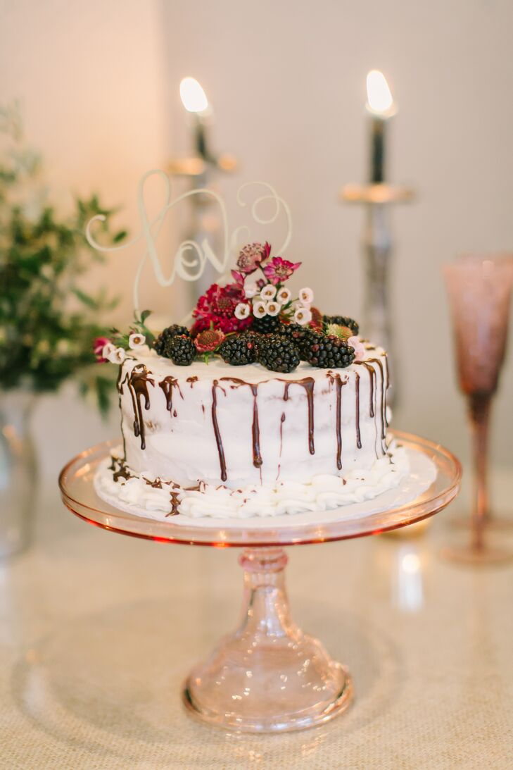 """I used to work at a wedding venue as a banquet server in high school, and I can remember couples having this huge fancy cake that we would cut and serve, but most of it got thrown out,""  Stefanie says. ""I vowed then that I would never spend money on an expensive, extravagant cake for my wedding."" Instead, the couple opted for a small one-tier cutting cake trimmed with fresh fruit, flowers and a ""Love"" cake topper. After dinner, the couple treated guests to a slice of white sheet cake with fresh berry filling and whipped cream—Chris's favorite treat. ""The sheet cake was delicious, and we saved a ton of money but still had a small pretty cake to display."""