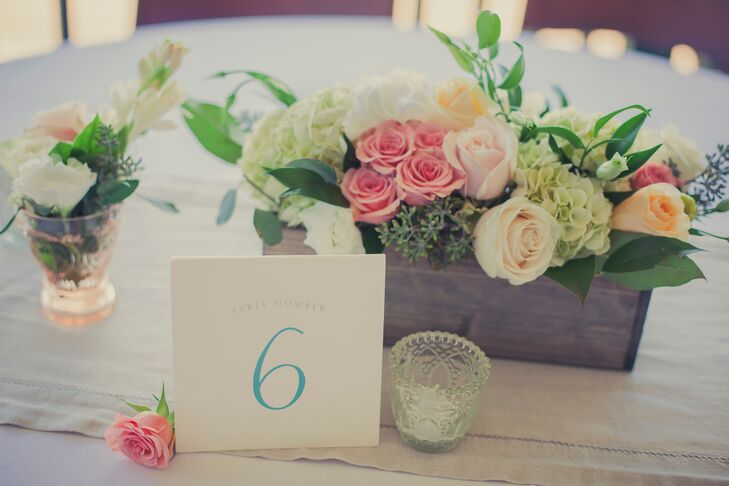 A blue and white table number was positioned in front of a wooden box centerpiece filled with a variety of pastel roses and hydrangeas.