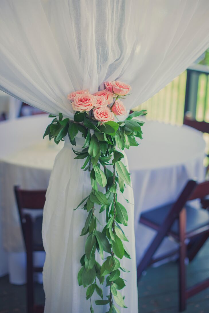 White draping at the reception was tied with a green garland accented with pink roses.