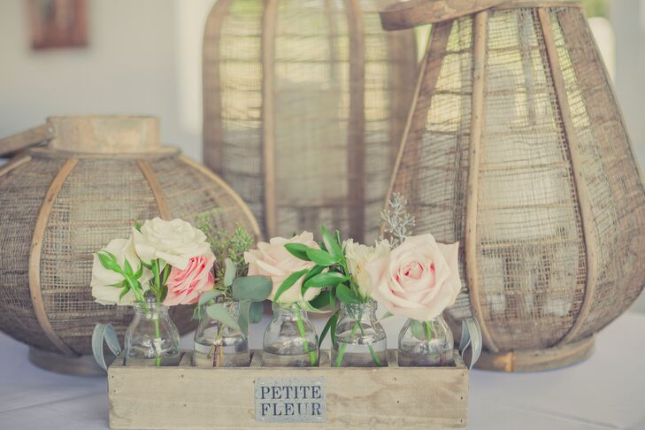 Pink and ivory roses were arranged in glass vases and placed inside a rustic wooden box. Behind the box were tall lanterns made of branches with candles inside.