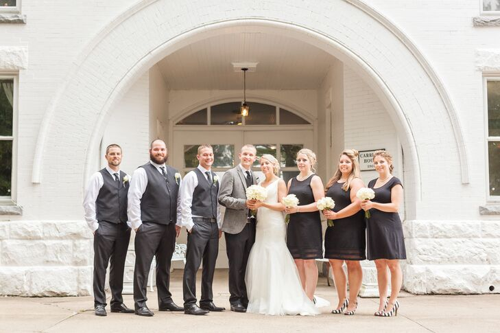 Anna and Tyler stood in the middle of their wedding party dressed in black-and-white attire, following the color palette of the wedding day. The groomsmen wore charcoal gray vests and pants and the bridesmaids wore black knee-length cocktail dresses.