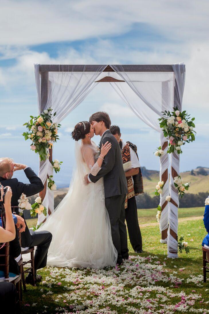 First Kiss Underneath Elegant Wedding Arch