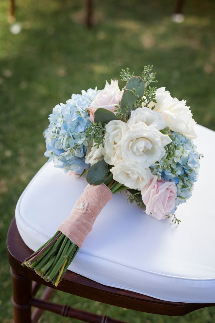 Tara held an ivory, blue and pink bouquet filled with roses and hydrangeas. The bouquet had a pink wrap.