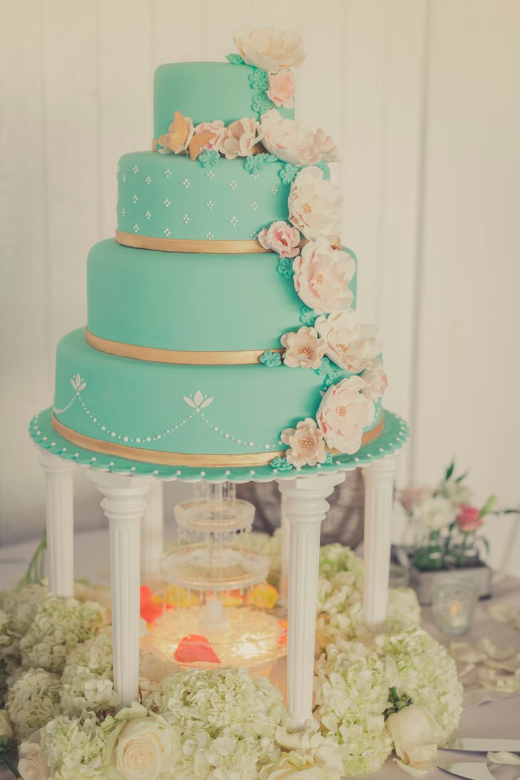 The intricate blue four-tiered wedding cake was designed with cake flowers and gold ribbon at the base of each tier. The cake stand was designed to look like white pillars with a mini fountain in the middle, surrounded by flowers.