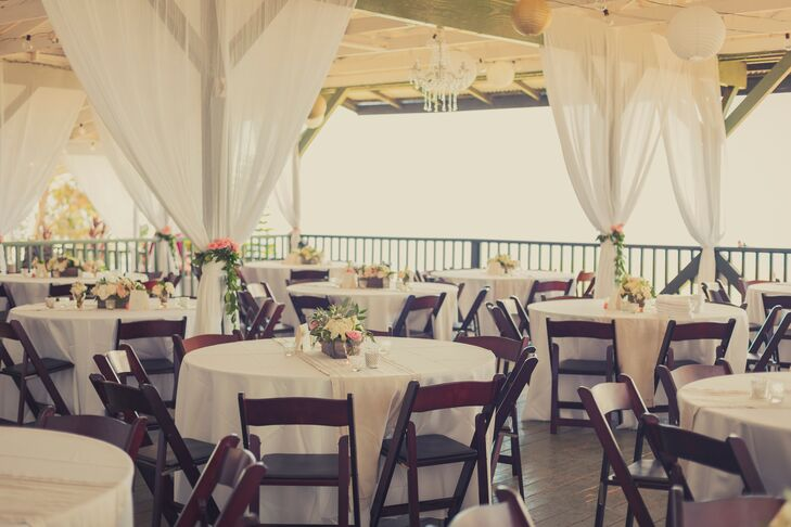 At Kahua Ranch, the reception took place on the patio that was decorated with white drapery. Dining tables were dressed in white tablecloths with petite flower arrangements.