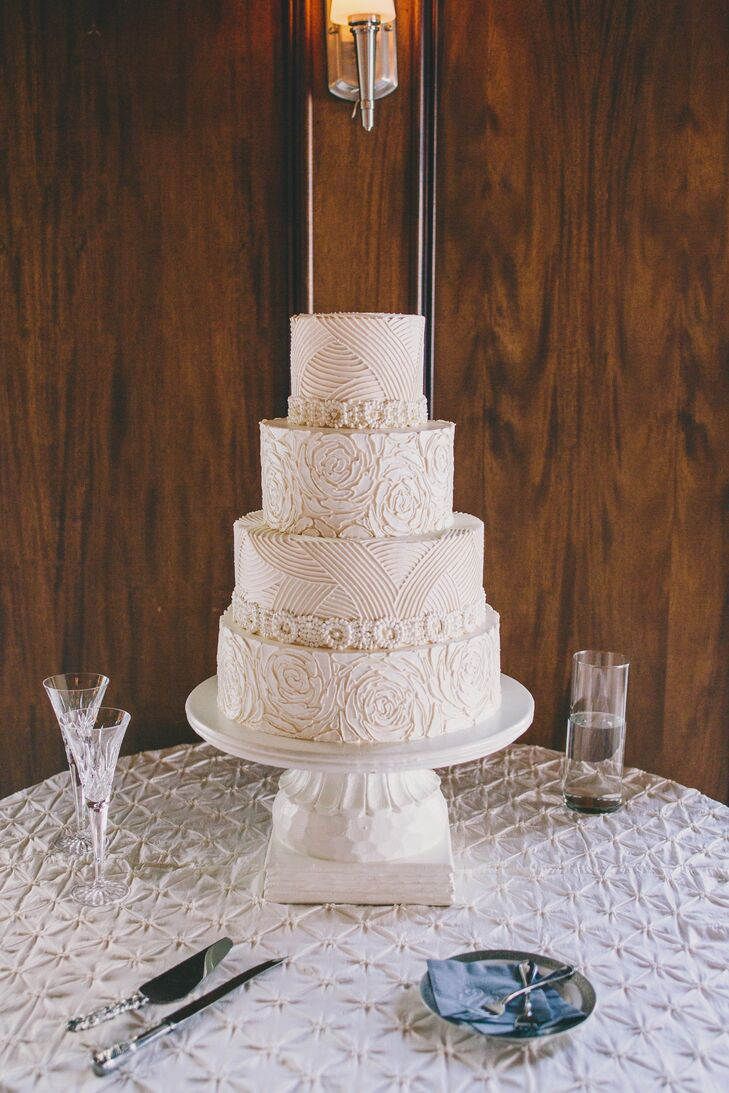 Wedding Cakes by Jim Smeal created a gorgeous, ornate four-tier white cake. Kinsey and Collins wanted the cake to echo the design of Kinsey's stunning Amsale ball gown. The cake alternated between rosettes and geometric stripes.