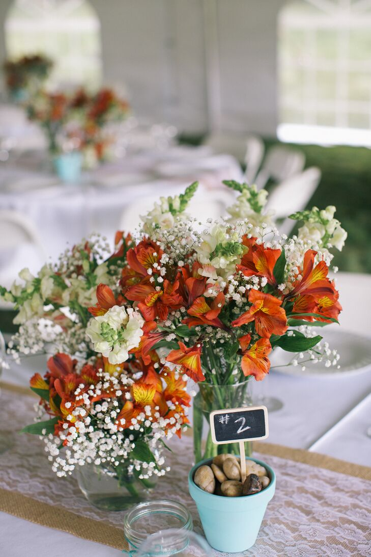 The centerpieces at the backyard reception included coral alstroemeria lilies, white snapdragons and baby's breath in small glass jars. Table numbers were indicated by chalkboard signs planted in pots filled with pebbles.
