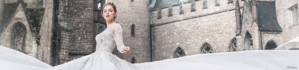 bride in Disney Fairy Tale wedding dress standing in front of the castle