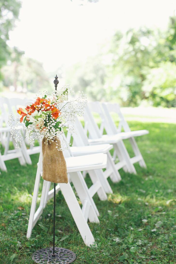 The aisles at the ceremony were decorated with hanging flower arrangements of alstroemeria and baby's breath in small burlap sacks.
