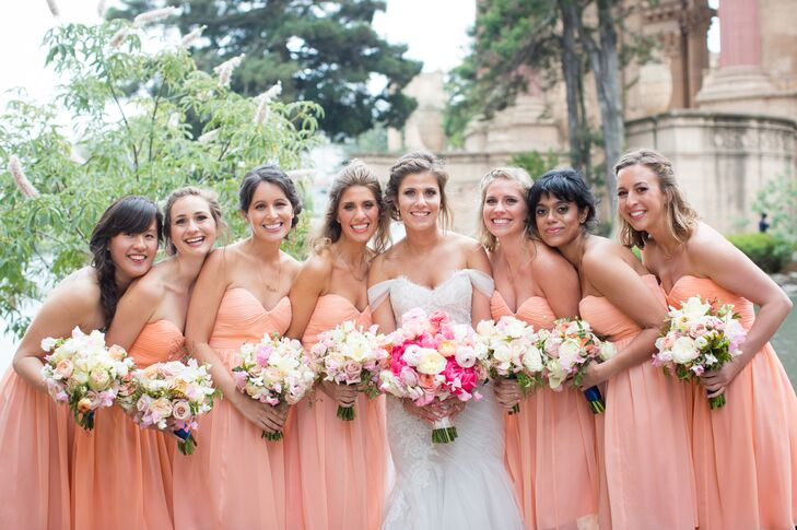 The bridesmaids matched in both peach color and strapless style. They selected their dresses from Donna Morgan, and each held a round bouquet filled with ivory blooms that popped against the peach gowns.