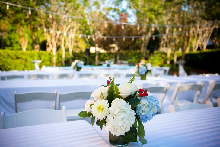 Centerpieces filled with a fresh mix of blue and white hydrangeas accented by red hypericum berries brought a light preppy touch to the reception tabletops.