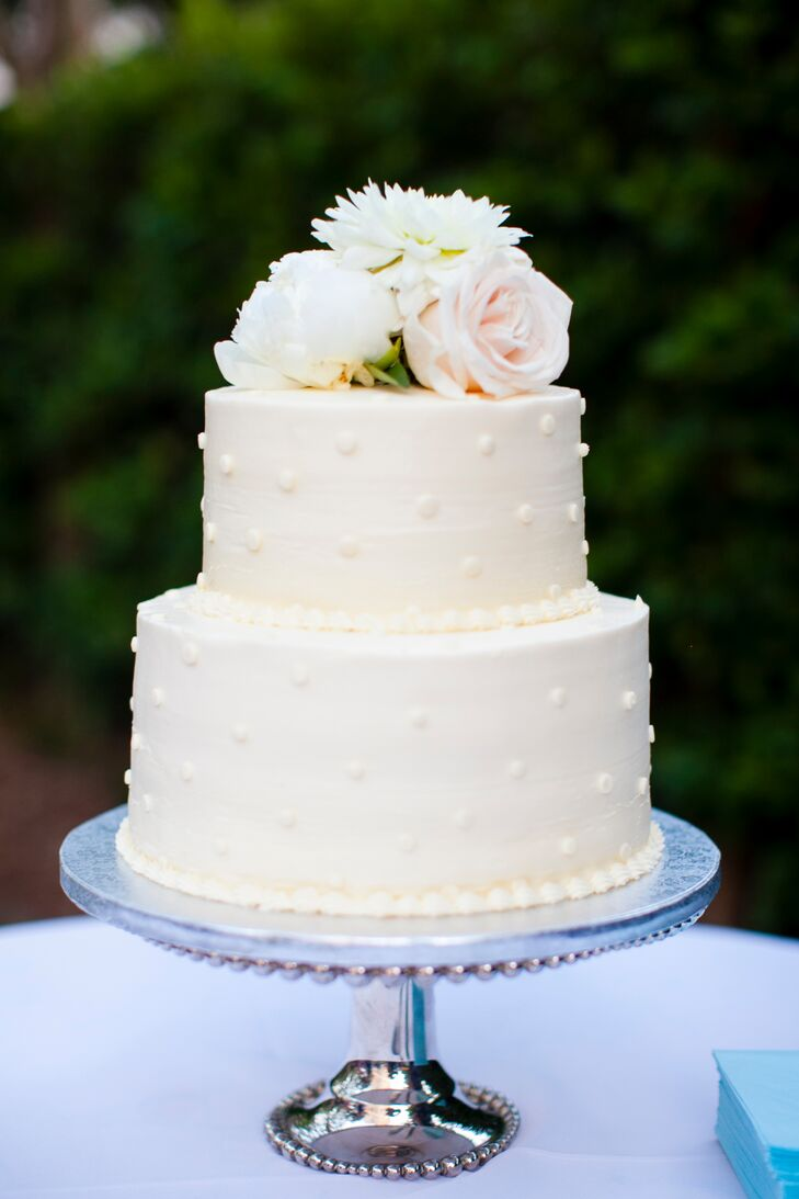 The two-tier buttercream wedding cake was decorated with ivory frosting, playful buttercream polka dots and topped with a fresh bunch of pastel roses and peonies.