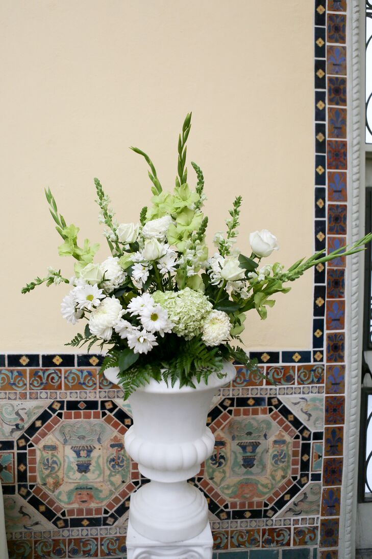 Large floral arrangements in white vases outside the venue had a mix of white and green daisies, hydrangeas, roses and lilies.