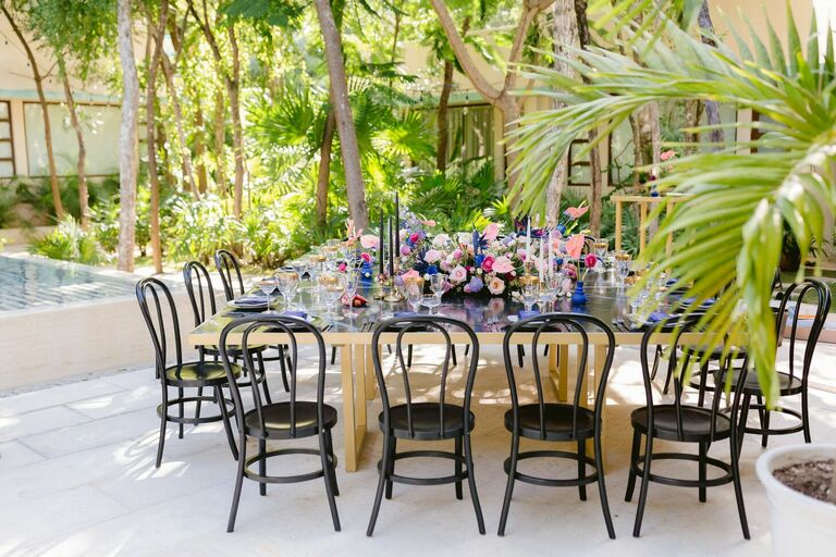 Glam beach reception with black bentwood chairs and gold table