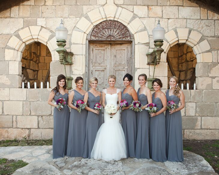 The bridesmaids wore soft slate one shoulder floor length chiffon gowns with plum-colored drop earrings from the bride to complete the elegant look.