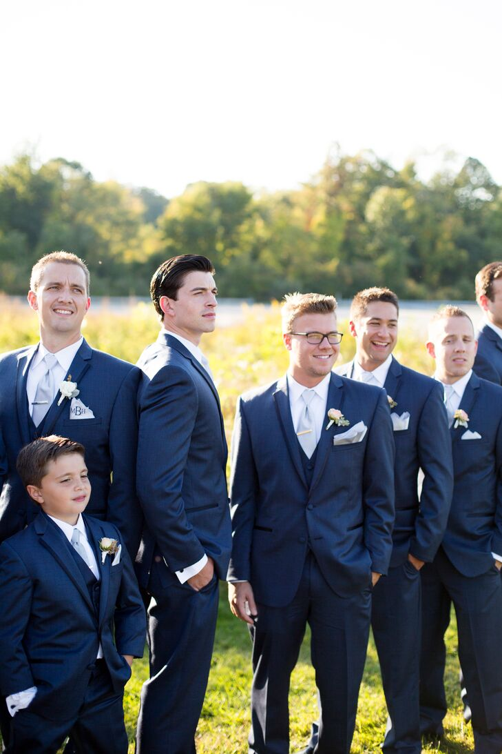 """When it came to his wedding day style, James headed to Stackpole Moore Tyron in Hartford, Connecticut, where MacKenzie's father used to buy all his suits. """"He was excited to pick his suit and he wanted to do it on his own,"""" MacKenie says. """"I think he nailed it."""" James was immediately drawn to a dark blue number, which despite MacKenzie's initial reservations, tied in seamlessly with the steel gray Jenny Yoo bridesmaid dresses."""