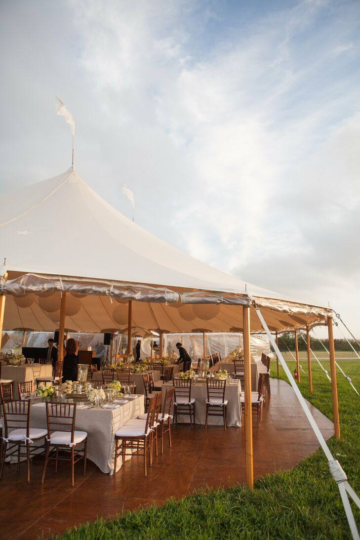 The reception was held at the same farm as the ceremony. A large tent was set up with various sized tables covered in light linen tablecloths. Small bouquets of white and light-green flowers were displayed on the tables as well as antique mirrors in the middle to reflect the light. Small antique silver and glass candle holders scattered across the tops of the tables.