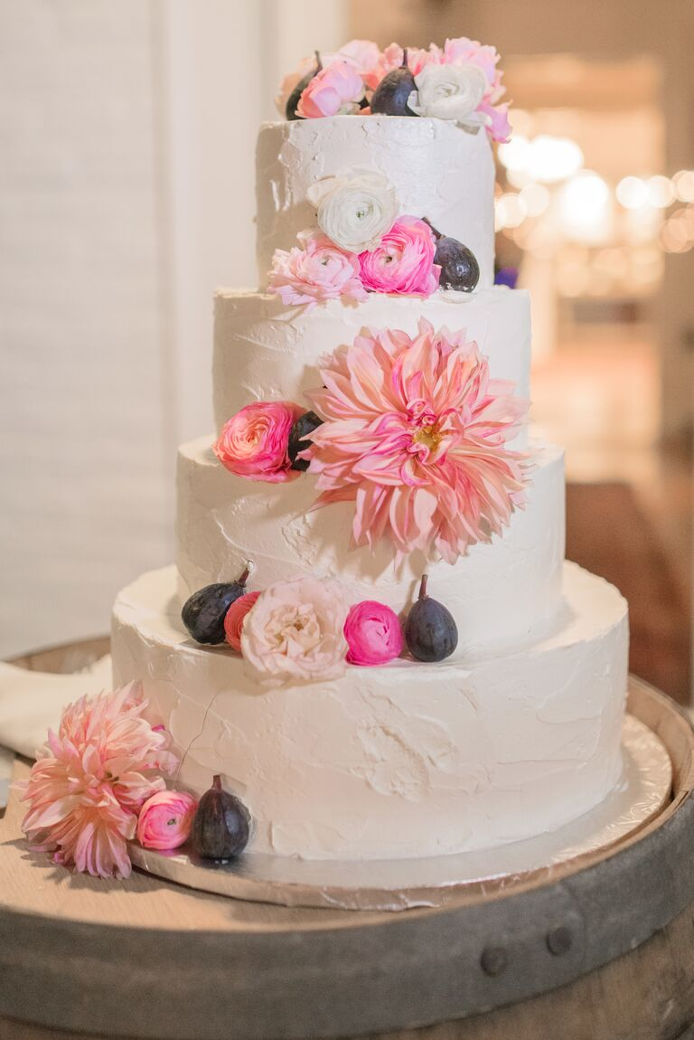Fresh flowers and figs on white four tiered wedding cake