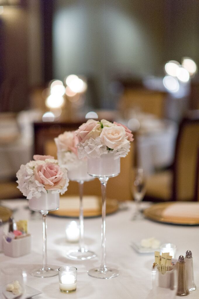 Each of the couple's linen covered tables was accented with three candlesticks filled with roses and hydrangeas in shades of pink and ivory.