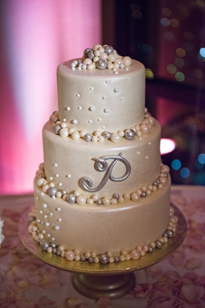 Allison and Jonathan served a white three-tiered wedding cake with purple and cream pearl detailing on each layer.
