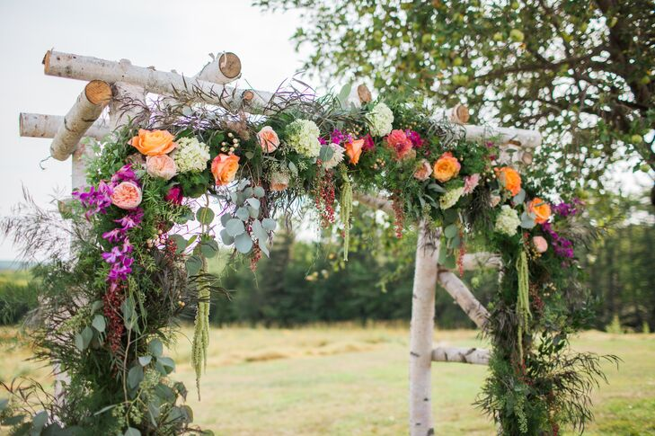 Using fallen brich trees, Samantha's father handcrafted the whimsical wedding arch under which the couple exchanged vows. A family friend then adorned the rustic structure with a lush garland of eucalyptus, wispy greenery, hydrangeas, garden roses, orchids and dahlias that brought a pop of fresh color to the scene.