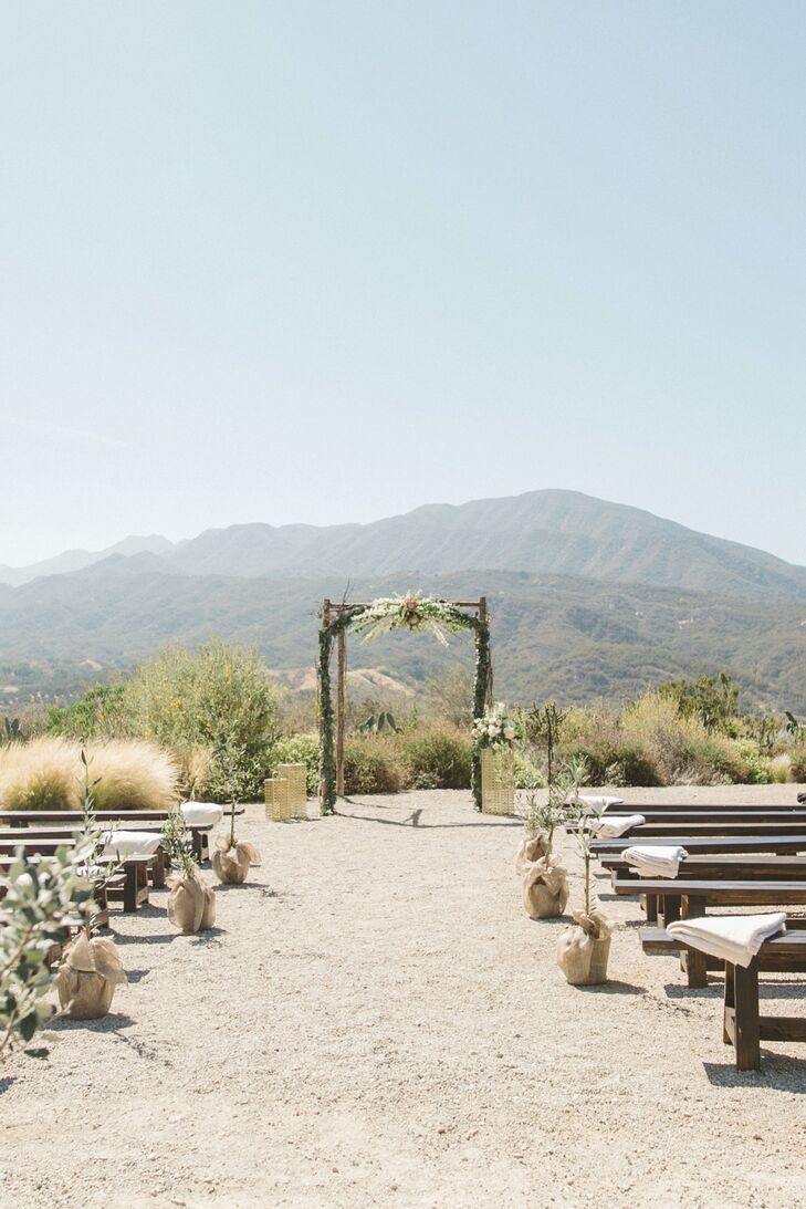 Tracy and Michael's outdoor ceremony at Red Tail Ranch in Ojai, California, overlooked miles of rolling hills. Burlap-bagged olive trees lined the aisle leading to the wedding arch, which was handcrafted from birch-wood branches and topped with a floral garlands. Throw blankets softened the look of the handmade wooden benches.