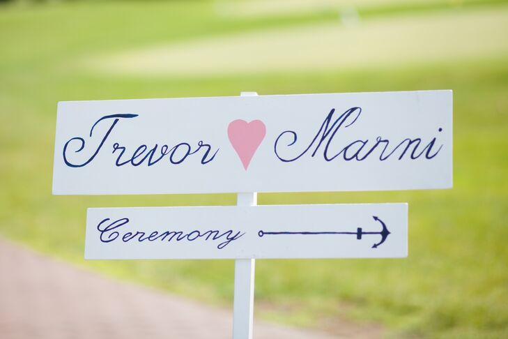 A white wooden sign directed guests to the outdoor ceremony.
