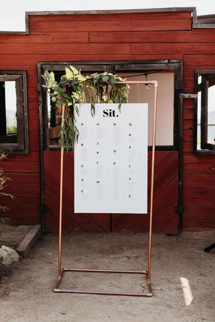 Rustic Seating Chart with Greenery Hanging from Copper Pipe Easel